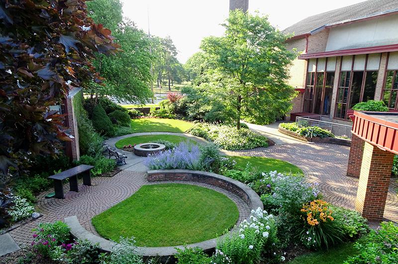 A green grassy garden with 2 circular short brick walls next to a large building