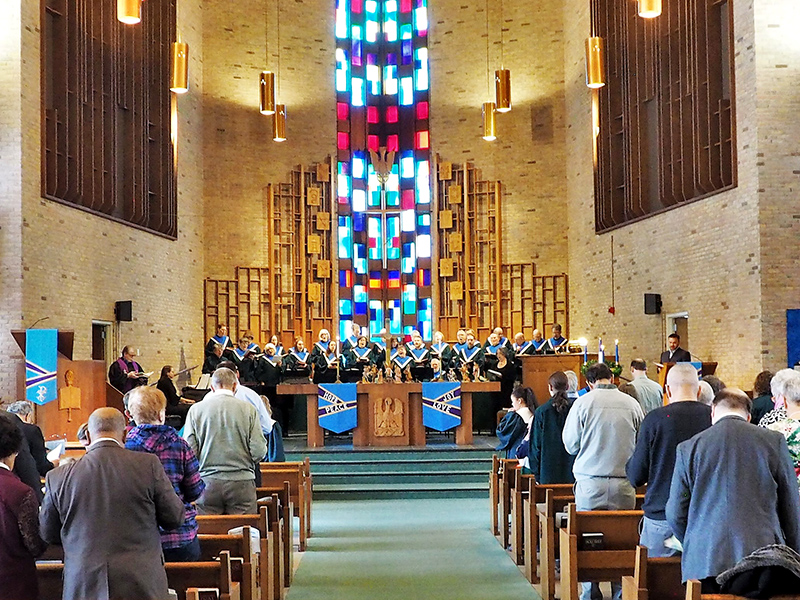 A church with stained glass windows and the choir singing.