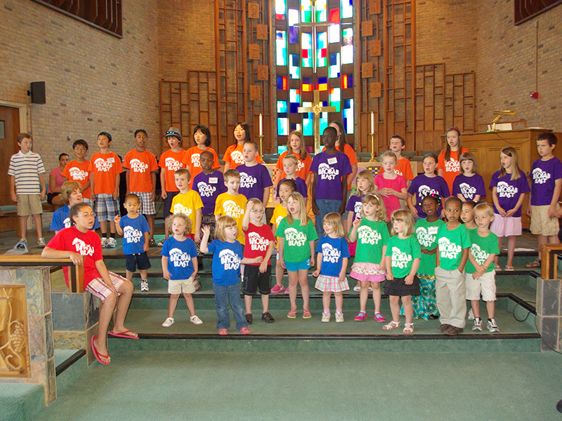 A group of children wearing brightly colored t-shirts.