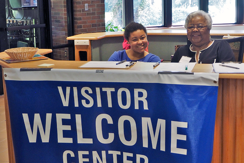 "Two smiling women sit behind a desk that has a sign that says ""visitor welcome center"""